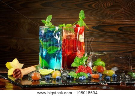 Close-up picture of blue and red drinks on black desk. Tasty bright summer cocktails with mint twigs blueberries strawberries grapes ice and carambola in highball glasses on the wooden background.