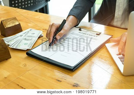 Businessman holding pen in hand pointing at contract sign,Businessmen putting hands on laptops have model houses and dollars on the desks.