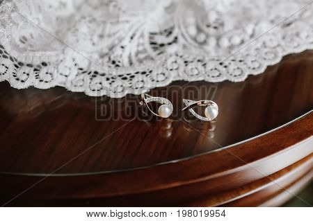 Bridal Pearl Earrings On Brown Wooden Table With White Wedding Veil