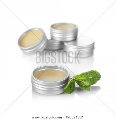 Containers with dry perfume and leaves of mint on white background