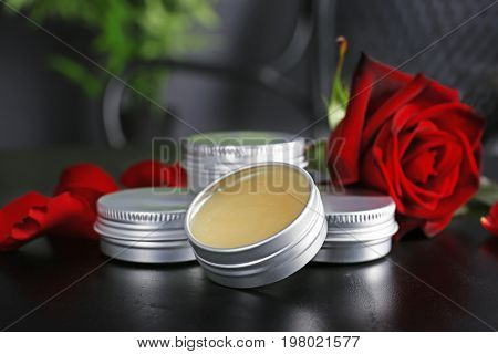 Containers with dry perfume and rose on dark table