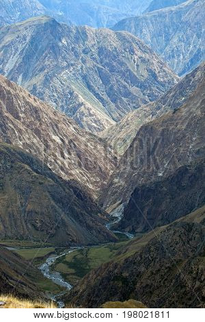 View of rocky gorge with steep slopes and wild river in Tien Shan in the autumn. Kyrgyzstan