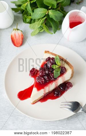 Cheesecake slice / piece of cheesecake with sweet cherry sauce on top. Vertical