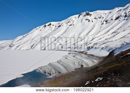 Helicopter from the hot springs on the shore of Karymsky lake in spring in Kamchatka Russia