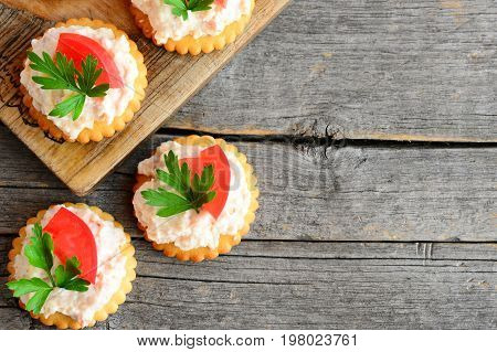 Home mini sandwiches with cream cheese on a wood background with empty place for text. Quick mini sandwiches from crackers cookies, spicy cream cheese, tomato and parsley. Tasty snack recipe. Top view
