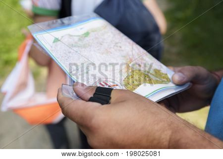 Orienteering in the forest. Man holding map