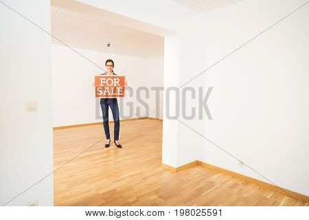 realtor in empty apartment, holding 'for sale' sign