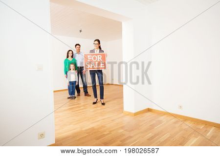 realtor and family in empty apartment, holding 'for sale' sign