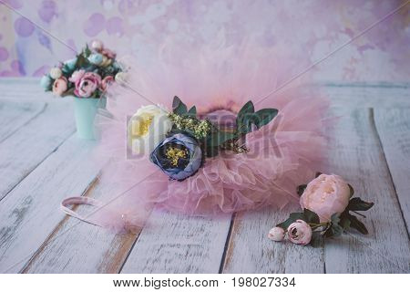 Pink Tu-tu Skirt For Newborn Babies And Headband With Fake Flowers Lying On Wooden Plank Floor