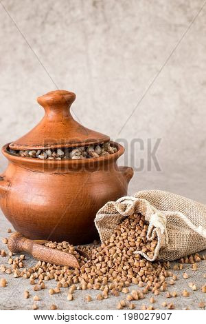 A small linen sack with raw buckwheat and a clay pot with hot buckwheat porridge on a gray background. Traditional Russian cuisine. The concept of a healthy diet.