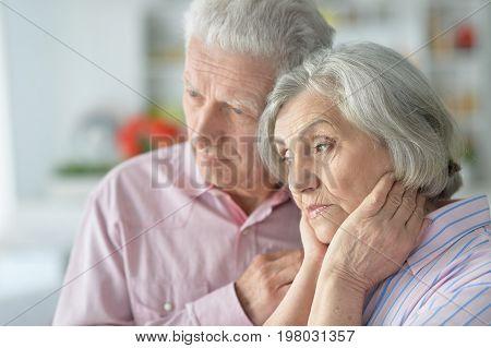 Portrait of sad senior couple, man holding hand on chin