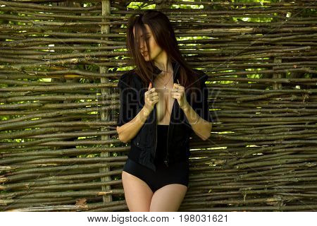 young Sexy brunette in black suit poses near a wooden fence
