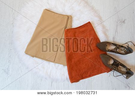 Two Brown Suede Skirt And Shoes On A White Fur. Fashionable Concept