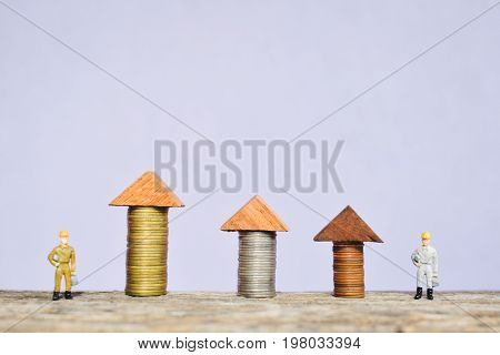 miniature worker team and and coin on wood concept to save money for my home soft focus