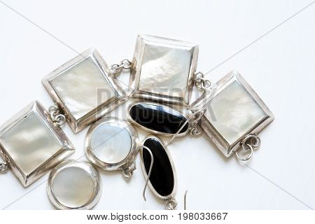 Set of various silver jewelry adornments on white wooden background with free space