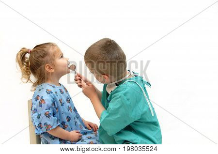 Little girl and little boy pretend to be dentist and patient. They are wearing a gown and scrub and boy is looking in mouth with mirror.