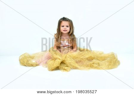 Little girl sits on a cloud of gold ribbon and tule. She is sitting in an all-white room in a pink gown.