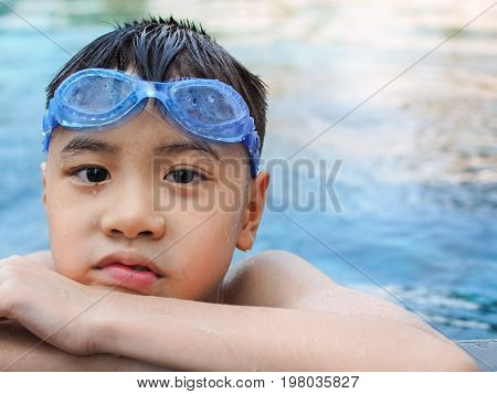 Asia boy kid child nine years old in swimming pool. Outdoor view