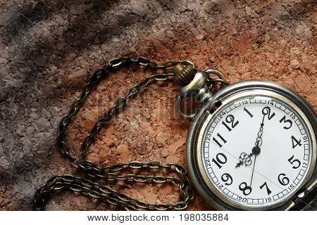Old pocket watch on cork wooden background