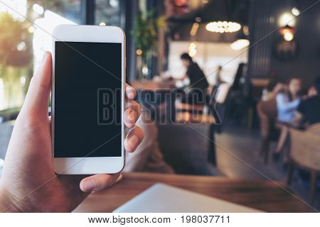 Mockup image of a man's hand holding and raising a white mobile phone with blank black screen in cafe with many people in background
