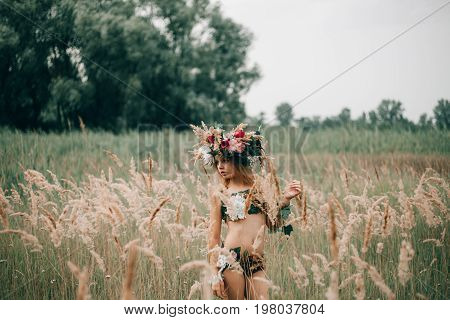 Beautiful little girl in image of nymph with floral head wreath stands among grasses on meadow.