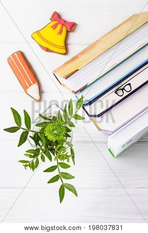 Hello, September. Books, bookmark glasses, gingerbread pencil and yellow bell, green chrysanthemum on a white wooden background