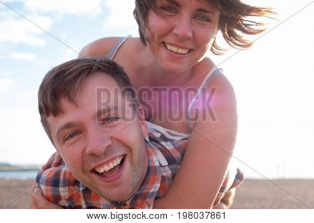 Happy couple on the beach. Girl holds her boyfriend on back. He outstretchs arms