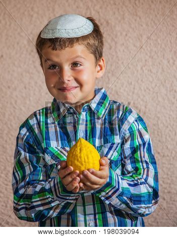Citron - ritual fruit for the Jewish holiday of Sukkot. Beautiful seven year old boy in white knitted skullcap is holding citrus