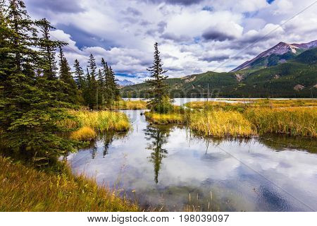 The smooth water of the lake reflects the cloudy sky. Magnificent journey through the Rocky Mountains of Canada. Concept of active and ecological tourism