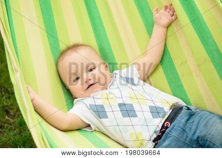 baby laughing in hammock in summe day