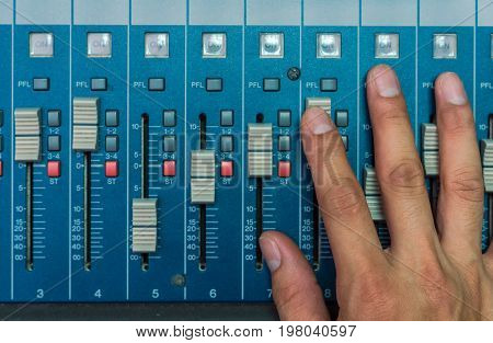Top view of Hand adjusting audio mixer music instrument concept
