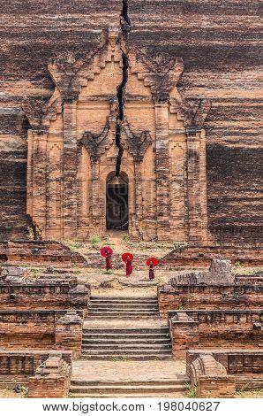 Three Buddhist novice are walking and holding the red umbrella at Mingun Pahtodawgyi bagan mandalay myanmar