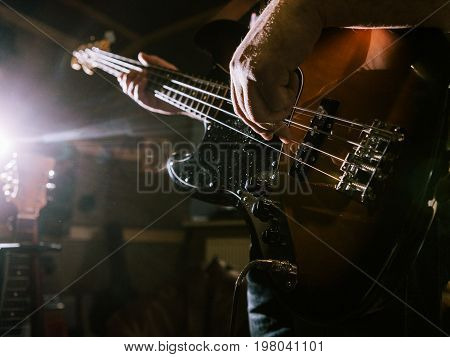 Playing bass guitar strings closeup. Unrecognizable guitarist, music recording studio, dark atmosphere with back light