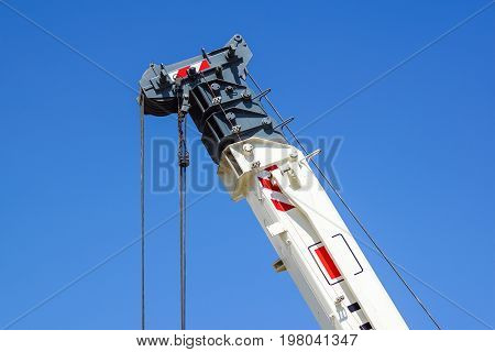 truck crane detail boom with hooks and scale weight above blue sky .