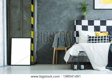 Design chair between king-size bed and metal shelf against concrete wall in creative bedroom