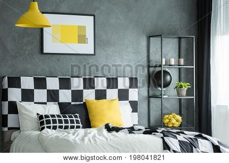 Black shelf with citrus black globe plant and candles next to black and white king-size bed