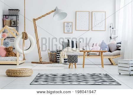 Cozy girly pastel bedroom of child with wooden furniture