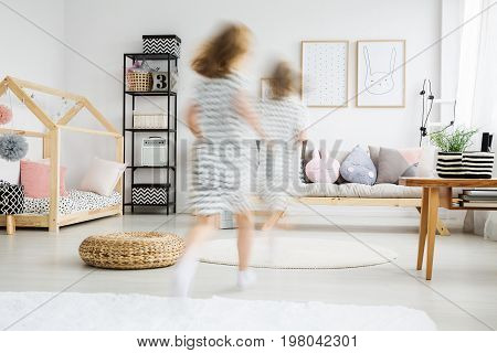 Blurred view of energetic young girl in dress running in trendy room with plush pillows
