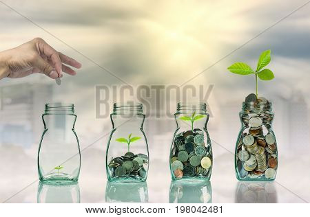 Hand putting mix coins and seed in clear bottle on cityscape photo blurred cityscape backgroundBusiness investment growth concept