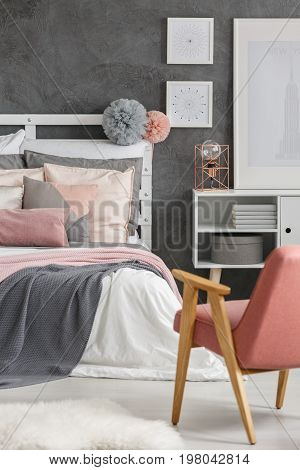Two fluffy pompoms hanging on wooden bedheads in room with posters