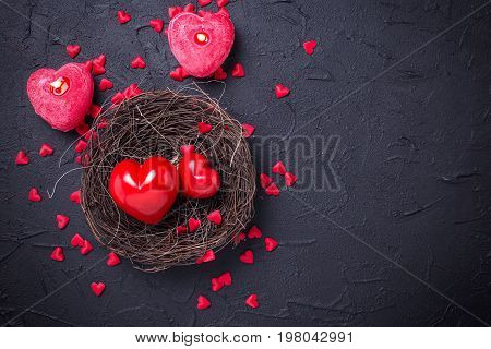 Red hearts in nest and candles in form of heart on black slate background. Top view. St. Valentine day background. Place for text.