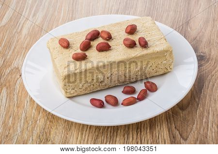 Peanuts And Piece Of Peanut Halva In Plate On Table