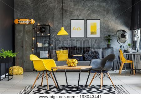 Modern furniture in unique yellow and gray industrial office interior