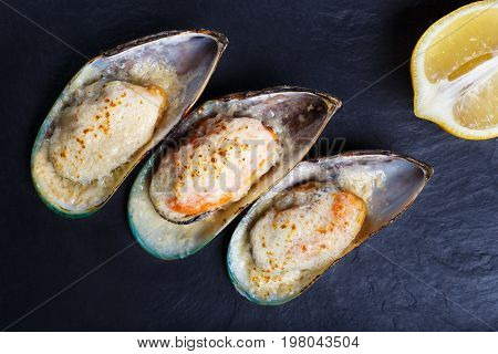 Baked Shellfish Mussels With Slice Of Lemon On Black Stone Table