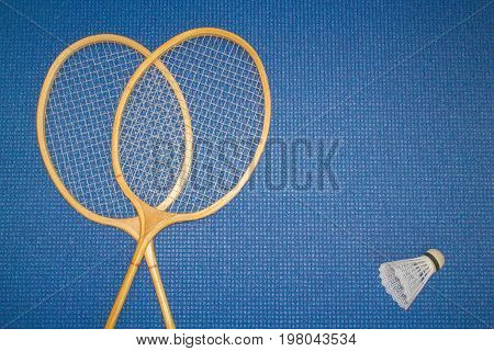 Blue background. Mat for sport yoga and meditation. Two badminton rackets and shuttlecock.