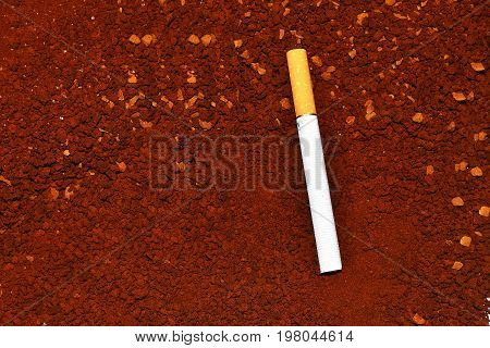 One cigarette in the background of instant coffee