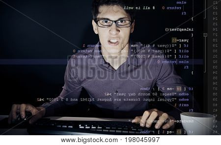 young man with glasses sitting in front of his computer, programming. the code he is working on unix shell script can be seen through the screen.