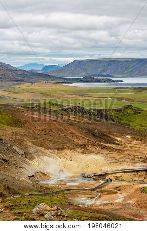KRISUVIK, ICELAND - AUGUST 27, 2016: Few people are enjoying geothermal place with hot springs at summer in South-Western Iceland