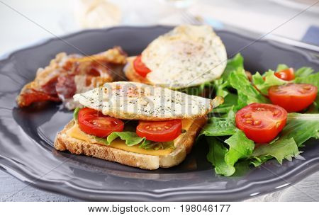 Plate with delicious egg sandwiches, vegetables and beacon on table, closeup