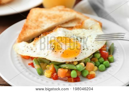 Plate with delicious over hard fried egg, toasts and vegetables, closeup